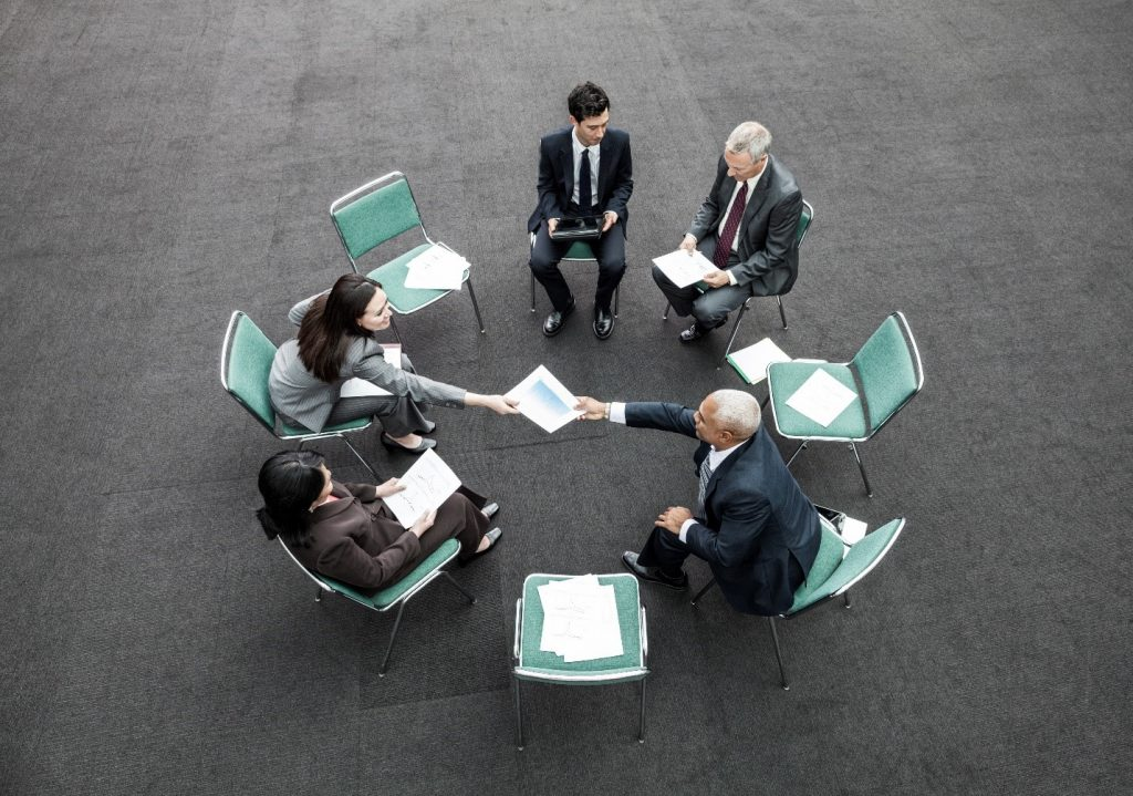 A diverse group of men and women sitting in a circle exchanging program handouts